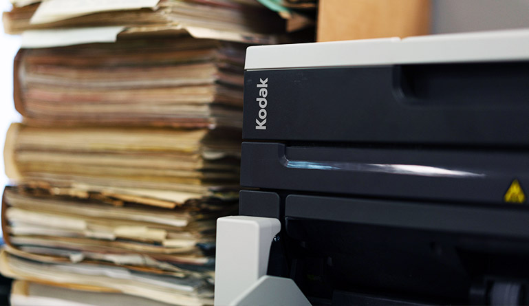 Stack of files next to a scanner
